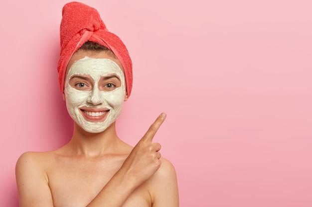 Mujer joven alegre con suave sonrisa, señala el dedo índice