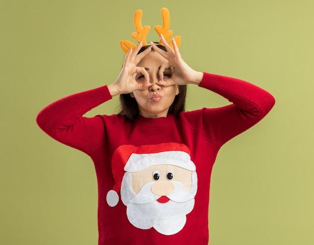 Mujer joven alegre en el suéter rojo de la navidad que lleva el borde divertido con los cuernos de venado a través de los dedos haciendo gesto binocular de pie sobre la pared verde