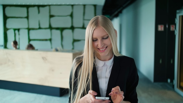 Mujer joven alegre con teléfono en la oficina mujer bonita rubia con cabello largo con elegante traje negro y sonriendo encantadoramente a la cámara dentro de la oficina moderna