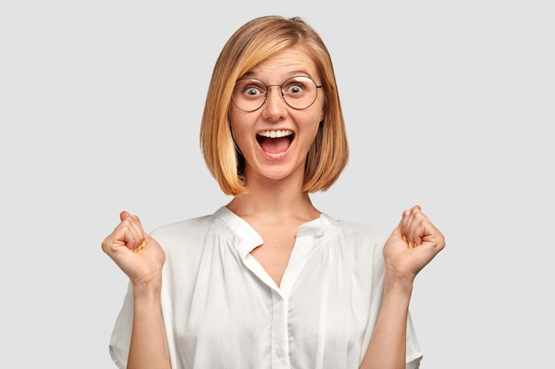 La mujer joven alegre tiene una expresión positiva, aprieta los puños, tiene una mirada llena de alegría, está muy animada, viste una camisa blanca, aislada sobre una pared blanca. gente, felicidad, concepto de éxito