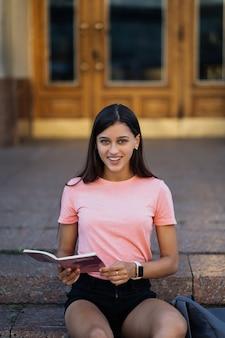 Mujer joven alegre tomando notas mientras está sentado en los pasos en la calle