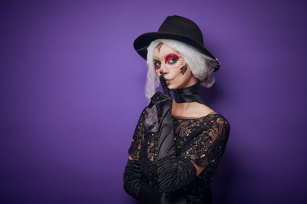 Mujer joven alegre en traje de halloween susurrando