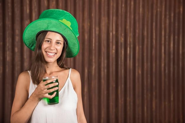 Mujer joven alegre con vaso de bebida
