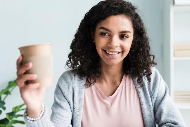 Mujer joven alegre con vaso de papel en la habitación