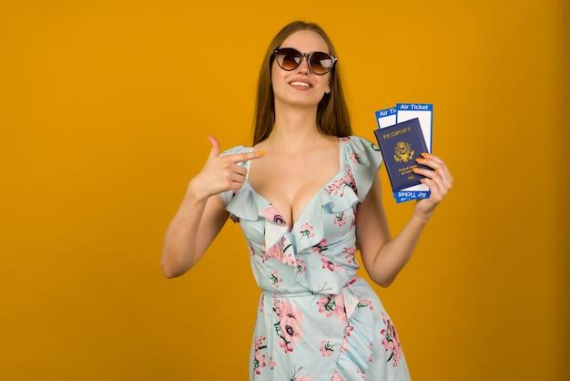 Mujer joven alegre en vestido azul con flores y gafas de sol apuntando a billetes de avión con pasaporte sobre un fondo amarillo. se regocija por la reanudación del turismo después de la pandemia de coronovirus.