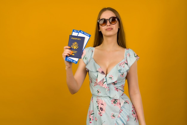 Mujer joven alegre en vestido azul con flores y gafas de sol sostiene billetes de avión con pasaporte sobre un fondo amarillo. se regocija por la reanudación del turismo después de la pandemia de coronovirus.