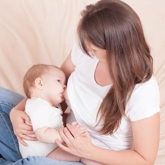 Una mujer joven alimenta el pecho del bebé, sentado en la cama.