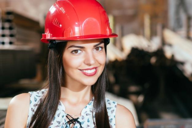 Mujer joven en un almacén con un casco de seguridad