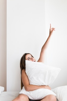 Mujer joven con almohada sentada en la cama apuntando hacia arriba