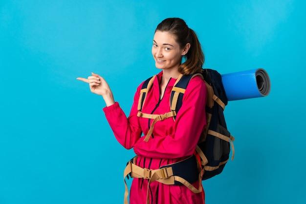 Mujer joven alpinista aislado dedo acusador hacia el lado