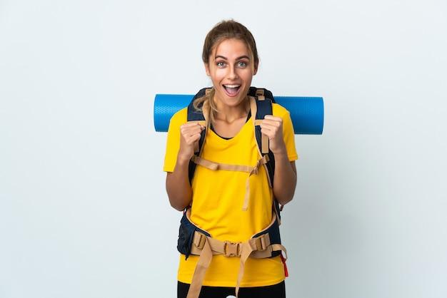 Mujer joven alpinista con una gran mochila aislada en la pared blanca celebrando una victoria en la posición ganadora