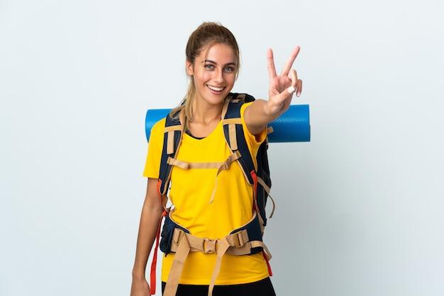 Mujer joven alpinista con una gran mochila en blanco sonriendo y mostrando el signo de la victoria