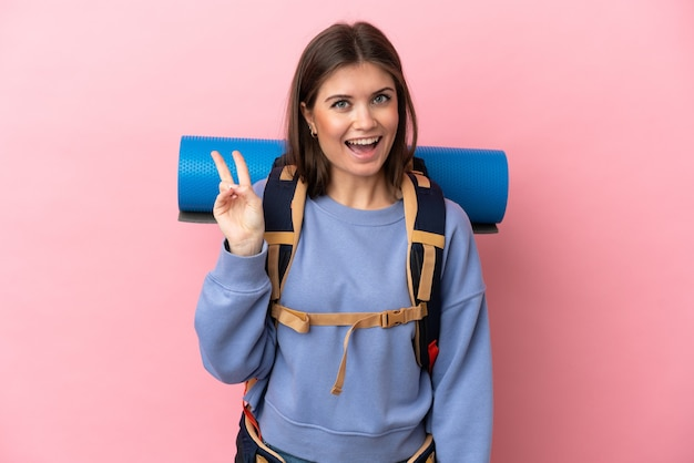 Mujer joven alpinista con una mochila grande aislada sobre fondo rosa sonriendo y mostrando el signo de la victoria