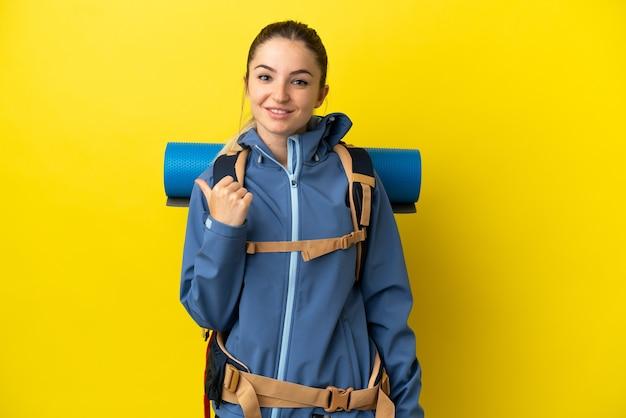 Mujer joven alpinista con una mochila grande sobre fondo amarillo aislado apuntando hacia el lado para presentar un producto