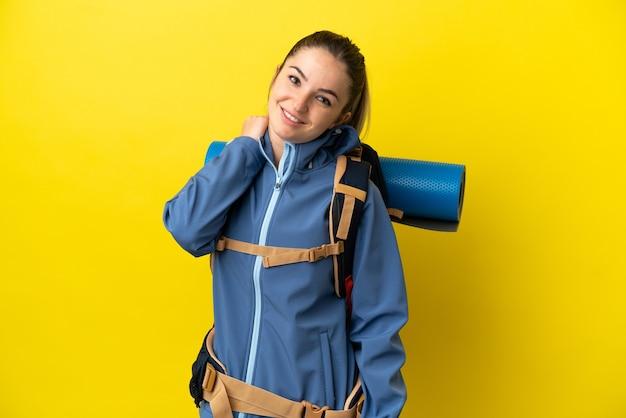 Mujer joven alpinista con una mochila grande sobre fondo amarillo aislado riendo