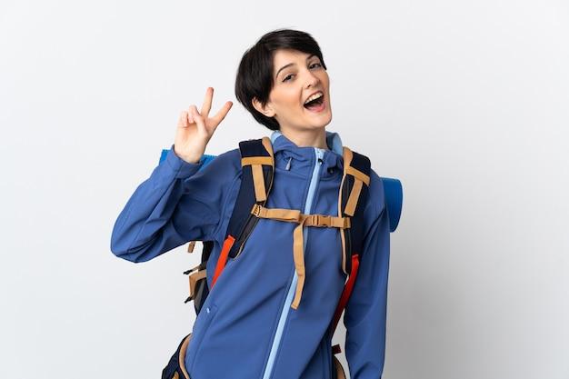 Mujer joven alpinista sobre pared aislada sonriendo y mostrando el signo de la victoria