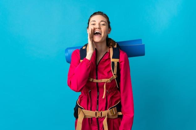 Mujer joven alpinista sobre pared azul aislada gritando con la boca abierta