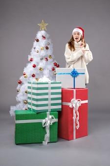 Mujer joven alrededor de regalos de navidad en el piso gris vacaciones de navidad de año nuevo