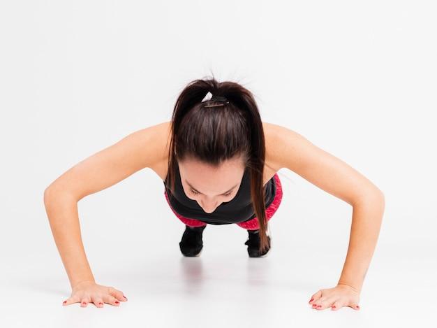 Mujer joven de alto ángulo haciendo flexiones