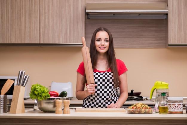 Mujer joven ama de casa trabajando en la cocina