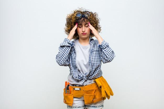 Mujer joven ama de llaves que parece concentrada, pensativa e inspirada, intercambiando ideas e imaginando con las manos en la frente en la pared blanca