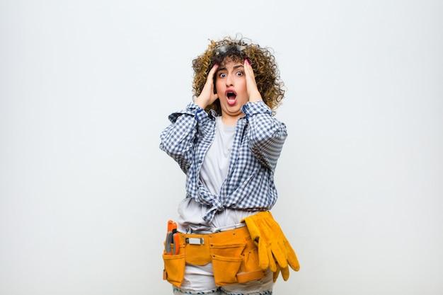 Mujer joven ama de llaves sintiéndose horrorizada y conmocionada, levantando las manos a la cabeza y entrando en pánico ante un error sobre la pared blanca