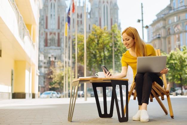 Mujer joven ambiciosa trabajando en una terraza