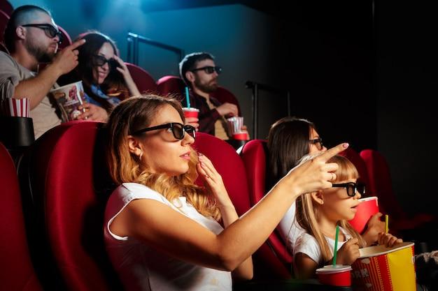 Mujer joven con amigos viendo una película en el cine