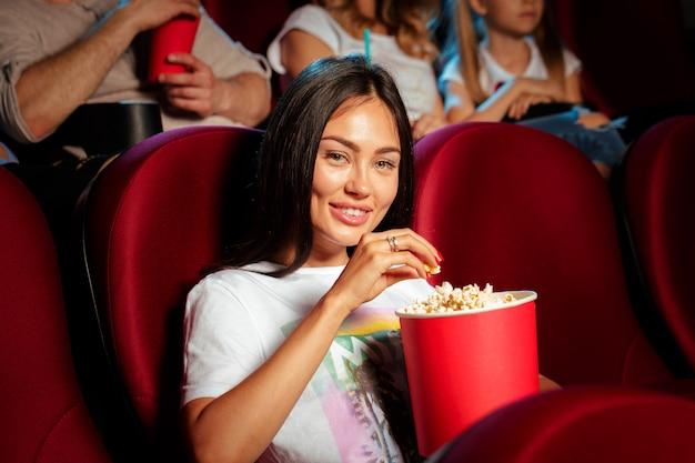 Mujer joven con amigos viendo películas en el cine