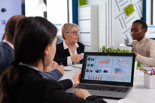 Mujer joven analizar gráficos en la computadora portátil en la puesta en marcha de la sala de reuniones de negocios