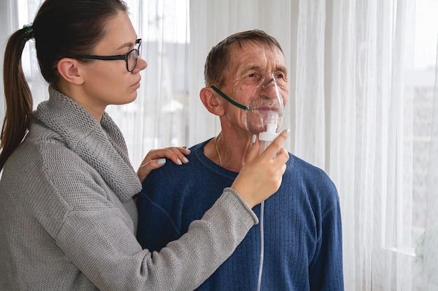 Mujer joven y anciano con máscara de oxígeno en cuarentena