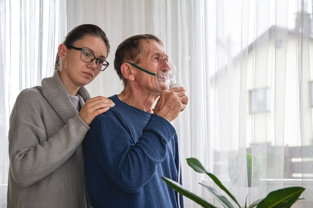 Mujer joven y anciano con máscara de oxígeno en cuarentena en