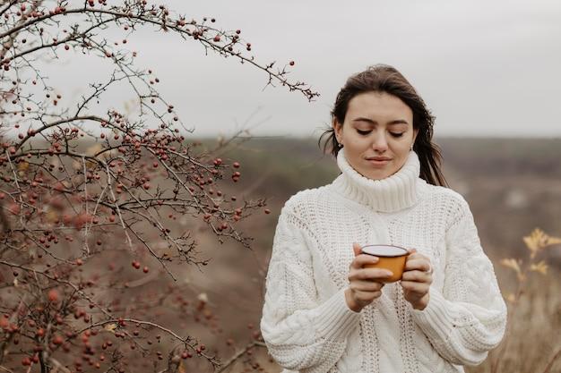 Mujer joven de ángulo bajo con té en taza