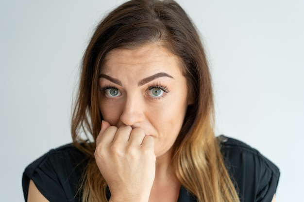 Mujer joven ansiosa preocupada que se preocupa y que mira la cámara.