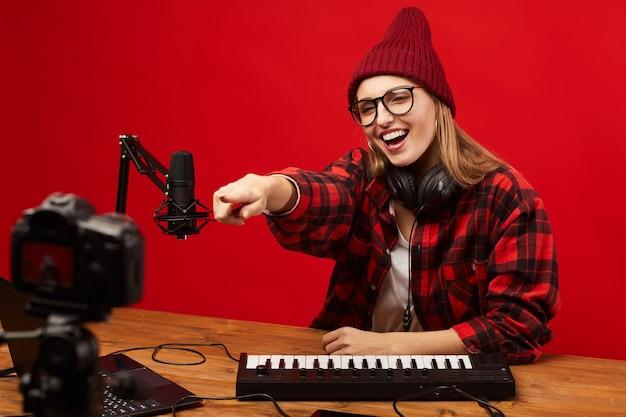 Mujer joven en anteojos sentado en la mesa y apuntando a la cámara de video que habla con gente en línea