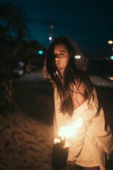 Mujer joven con antorchas en la playa por la noche