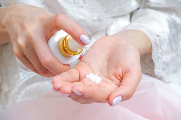 Mujer joven aplica crema de manos de un tubo de crema
