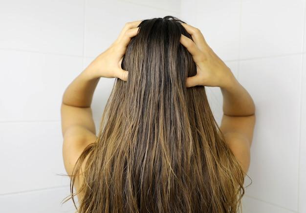 Mujer joven aplicando aceite para el cabello con los dedos. engrasar el cabello antes del lavado. concepto de cuidado del cabello.