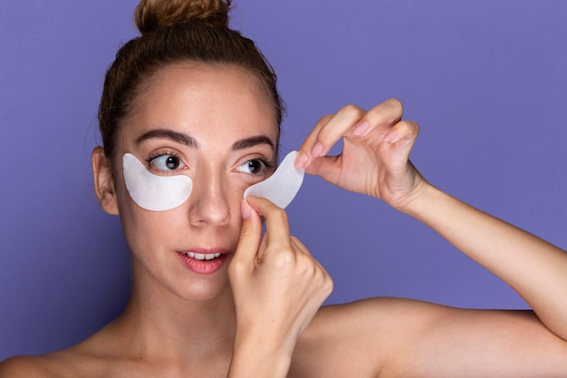 Mujer joven aplicando almohadillas para los ojos