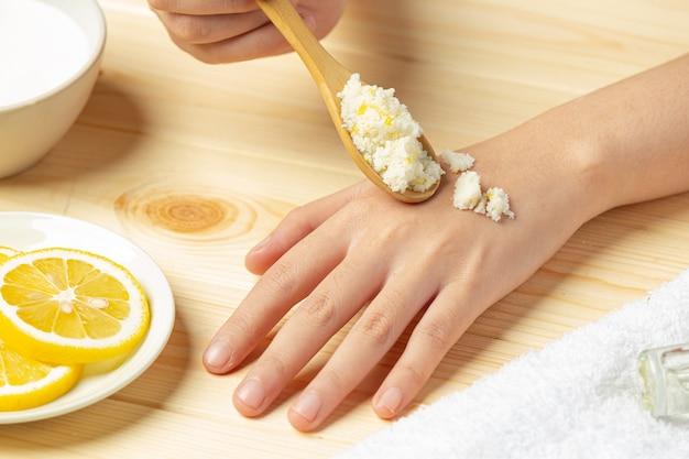 Mujer joven aplicando exfoliante de limón natural en las manos contra la mesa de madera