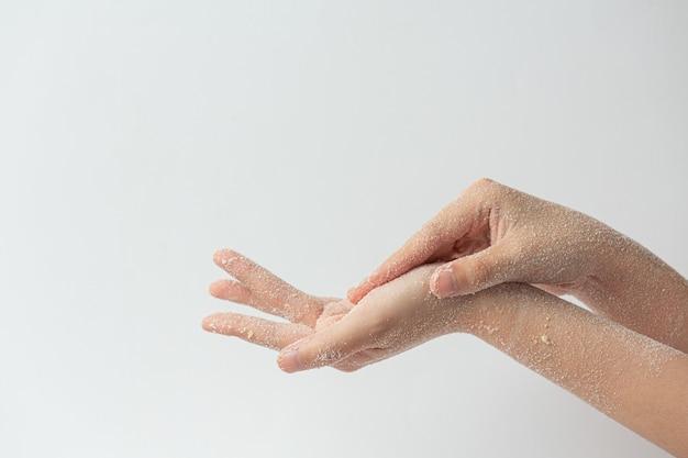 Mujer joven aplicando exfoliante de limón natural en las manos contra la superficie blanca