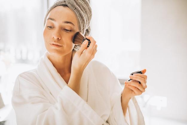 Mujer joven aplicando rubor y mirando en el espejo
