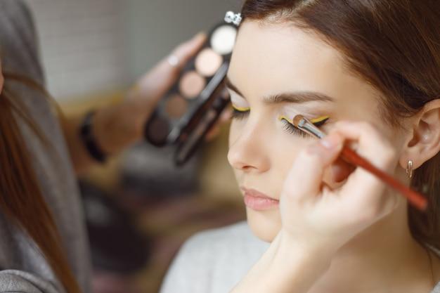 Mujer joven aplicar maquillaje al modelo en el salón