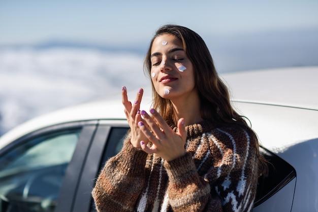 Mujer joven aplicar protector solar en la cara en el paisaje de nieve