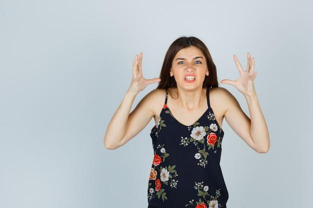 Mujer joven apretando los dientes, haciendo un gesto de enojo