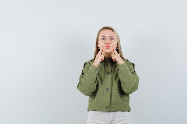 Mujer joven apretando sus mejillas en chaqueta verde, jeans y mirando enfocado. vista frontal.