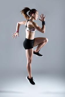 Mujer joven apta y deportiva que se ejecuta en el fondo blanco.