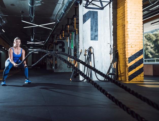 Mujer joven apta que ejercita con las cuerdas de la batalla