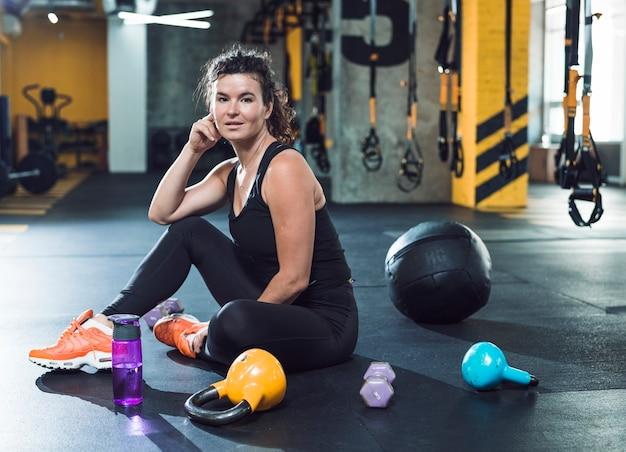 Mujer joven apta que se sienta en piso cerca de equipos del ejercicio en gimnasio