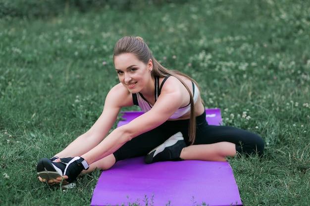 Mujer joven apta en ropa deportiva realiza estiramientos después de un entrenamiento fuera